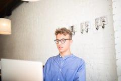 För websiteinnehåll för man som yrkesmässig skapare arbetar på bärbar datordatoren och att sitta i regeringsställning eller coffe royaltyfri foto