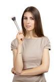 För Young för sminkkonstnär som borste för smink kvinna hållande isoleras arkivfoto
