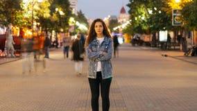 För zoom Time-schackningsperiod ut av det nätta flickaanseendet i fot- gata i höstafton med armar som korsas och ses arkivfilmer