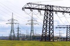 Föra för elektricitetspyloner som är aktuellt från fördelningskraftverk med dramatiskt kopieringsutrymme för molnig himmel royaltyfria foton