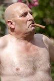 Föraktlig man med cigarren som är shirtless Arkivfoto