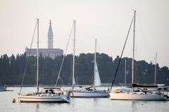 Förankrade segelbåtar framme av tornet för helgonEuphemia klocka Arkivfoto