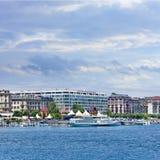 Förankrat vitt kryssningfartyg framme av lyxiga hotell, Genève, Schweiz Arkivbild