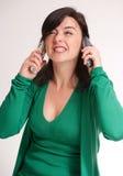 Förargad brunett som talar med två telefoner Royaltyfri Bild
