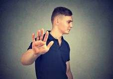 Förargad ilsken man med den dåliga inställningen som ger samtal till handgesten arkivfoton
