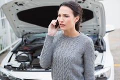 Förargad kvinna på telefonen bredvid hennes brutna ner bil Royaltyfri Foto
