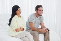 Förargad kvinna som ser upp under hennes pojkvän som spelar videospelet Arkivbild