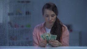Förargad medelålders kvinna som räknar pengar på den regniga dagen, besparingar för behandling arkivfilmer