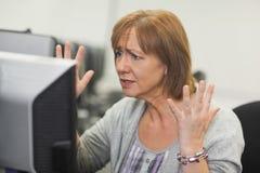 Förargad mogen kvinna som arbetar på datoren fotografering för bildbyråer