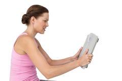 Förargad ung kvinna med viktskalan arkivbild