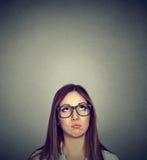 Förargad ung skeptisk kvinna som ser upp Royaltyfri Fotografi