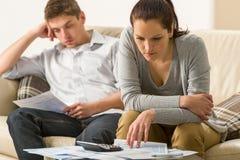 Förargade par som beräknar deras finanser Arkivfoto