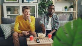 Förargade unga män afrikansk amerikan och Caucasian vänner håller ögonen på television med känslolösa framsidor och äter popcorn lager videofilmer