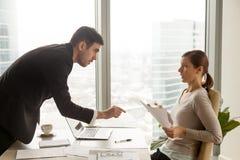 Förargat framstickande som argumenterar med kvinnlig anställd royaltyfri bild