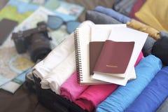 F?rbered tillbeh?r f?r ny resa som packar kl?der i resv?skap?se p? s?ng arkivfoto