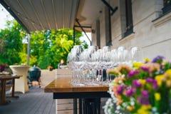 Förbereda en terrass för händelsen På sommarterrassen finns det tabeller med exponeringsglas Begreppet av ett parti, ett bröllop  Royaltyfri Foto