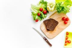Förbereda ljus grönsaklunch med körsbärsröda tomater, sallad, bröd, paprica på vit copyspace för bästa sikt för bakgrund Arkivfoton