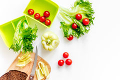 Förbereda ljus grönsaklunch med körsbärsröda tomater, sallad, bröd, paprica på vit copyspace för bästa sikt för bakgrund Arkivbilder