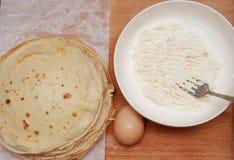 Förbereda process av läckra tunna traditionella rysspannkakor på trätabellen royaltyfri foto