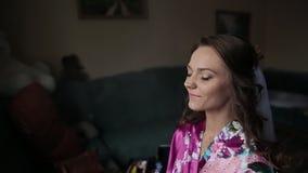Förbereda sig för bröllopberömmen Applicera makeup till brud`en s vända mot med den härliga bröllopfrisyren lycklig brud lager videofilmer