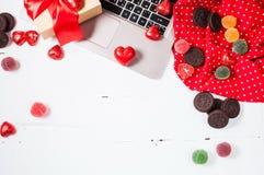 Förbereda sig för dag för St-valentin` s: bärbar dator, gåva, garneringar och godisar på en vit trätabell Royaltyfri Foto