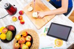 Förbereda smoothien, medan få online-information om nutrit royaltyfria foton