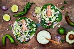 Förbereda sunda lunchmellanmål Fisktaco med den grillade laxen, den röda löken, nya salladsidor och avokadokoriandersås arkivbild