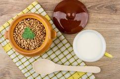 Förberedd bovete i den keramiska krukan, kopp av mjölkar och skedar Royaltyfri Bild