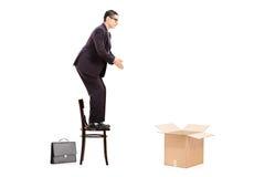 Förberedd manlig affärsman att hoppa i en tom ask Royaltyfri Fotografi