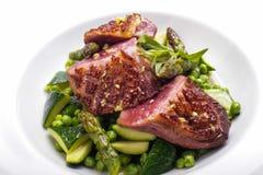 Förberedd nötköttbiff med grönsakgarnering arkivbilder