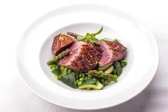 Förberedd nötköttbiff med grönsakgarnering arkivfoton