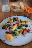 Förberedd platta av bläckfisken och tioarmade bläckfisken på tabellen av en restaurang royaltyfria bilder