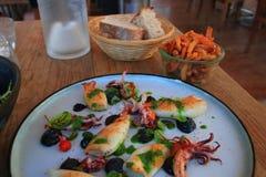 Förberedd platta av bläckfisken och tioarmade bläckfisken på tabellen av en restaurang arkivfoto