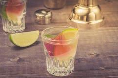 förberedelse av coctailen med en limefrukt i en shaker/en förberedelse av coctailen med en limefrukt i en shaker på en träbakgrun arkivbilder