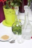 Förberedelse av den alkoholiserade coctailen Absint kallt vattenställning i glasflaskor på tabellen Nära tefatet med rottingsocke Arkivfoton