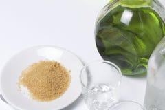 Förberedelse av den alkoholiserade coctailen Absint kallt vattenställning i glasflaskor på tabellen Nära tefatet med rottingsocke Arkivbild