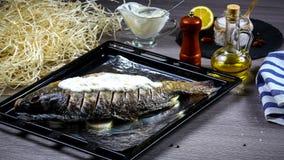 Förberedelse av den nya fisken för att baka med grönsaker och bevattnad gräddfilsås på en gammal bakplåt royaltyfri bild