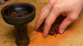 Förberedelse av en blandning av tobak för att röka vattenpipan tobakförberedelse i bunken av shisha Vattenpipatobak in arkivfoton