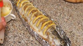 Förberedelse av fisken med citronen i olja lager videofilmer