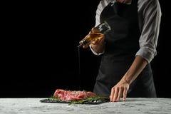 Förberedelse av kocken av biffkocken Förberedelse av nytt nötkött eller griskött Horisontalfoto med mörk svart bakgrund royaltyfri bild