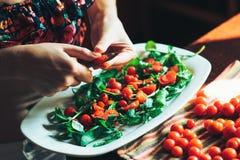 Förberedelse av ny sallad med tomaten, ruccola på ett köksbord Arkivfoto