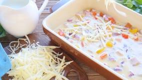 Förberedelse av omelettet med skinka och ost, innan att bakas lager videofilmer