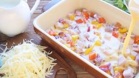 Förberedelse av omelettet med skinka och ost, innan att bakas stock video
