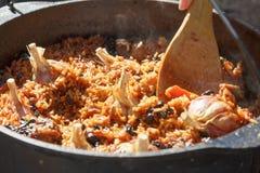 Förberedelse av pilaff på brand Turist- kastare med mat på brasan som lagar mat i vandringen som är utomhus- arkivbild