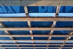 Förberedelse av taktaket för installation av ark av metalltegelplattor med isolering som waterproofing med hjälpen av filmen, brä royaltyfri foto