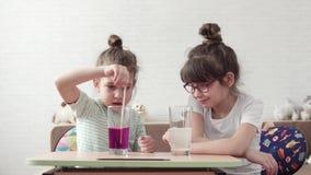 Förberedelse för experimentet Barnlek i laboratoriumet lilla flickan är rörda kemiska agens i ett exponeringsglas arkivfilmer