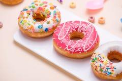 Förberedelse för ferien Färgrika amerikanska donuts på rosa lodisar Royaltyfri Fotografi