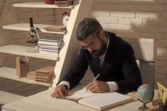 Förberedelse för skola Professorn i exponeringsglas med den allvarliga framsidan skriver i bok Arkivfoton