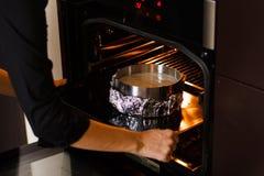 Förberedelse som bakar pajen Händer för man` s sätter formen med smeten in i ugnen Royaltyfri Foto
