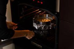 Förberedelse som bakar pajen Händer för man` s sätter formen med smeten in i ugnen Arkivfoto